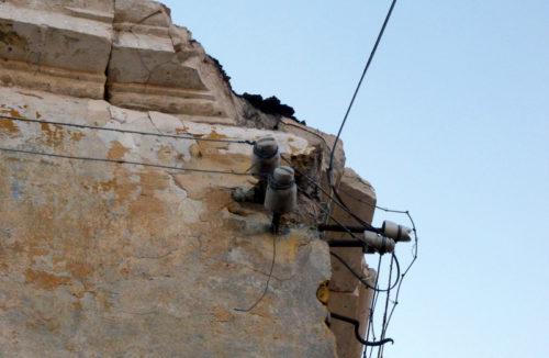 С фронтона сгоревшего дома падают куски известняка
